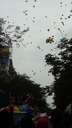 雨空に飛んでいく虹色の風船。