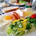 写真: 半熟目玉焼きとソーセージの朝食